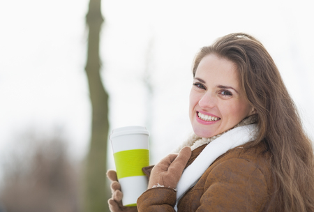Happy young woman enjoying cup of hot beverage in winter park photo