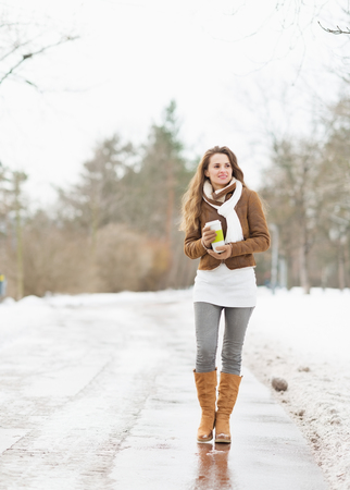 Happy young woman with cup of hot beverage walking in winter park photo