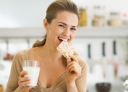 Happy young woman eating crisp bread with milk in kitchen photo