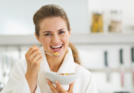 Smiling young woman in bathrobe having healthy breakfast photo