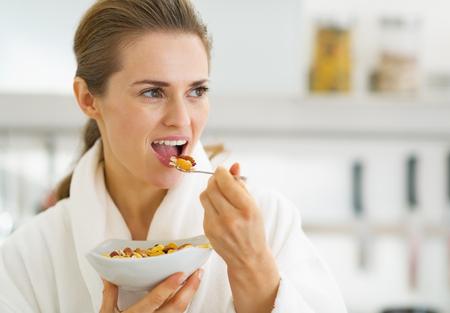バスローブのキッチンで健康的な朝食を持つ若い主婦