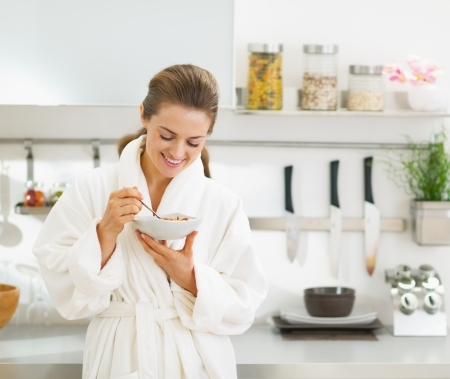 house robe: Smiling young housewife having healthy breakfast in modern kitchen