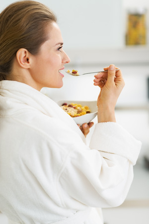 house robes: Young housewife in bathrobe having healthy in kitchen Stock Photo