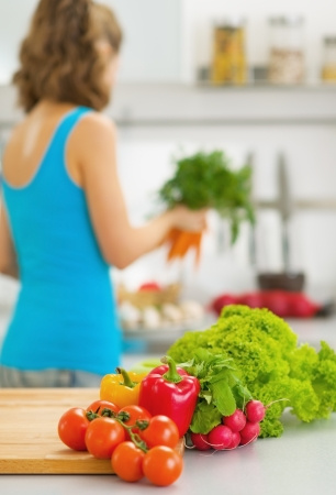 Closeup on vegetables on cutting board and young housewife in background photo
