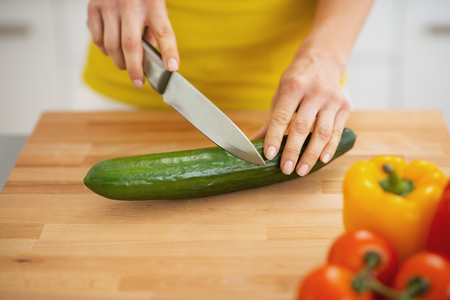 Closeup on woman cutting cucumber on cutting board photo