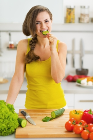 Happy young woman biting cucumber while cutting fresh salad Stock Photo