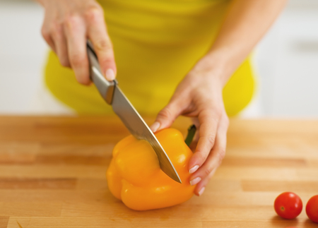 Closeup on woman cutting yellow bell pepper photo