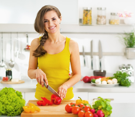 Happy young woman cutting fresh vegetable salad Imagens