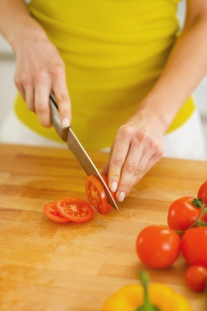 Closeup on young housewife cutting tomato on cutting board photo