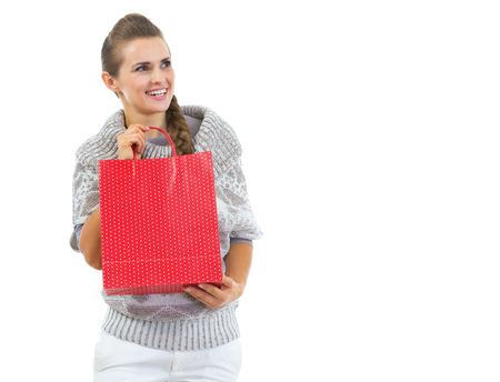 Happy young woman in sweater with red christmas shopping bag looking on copy space Stock Photo - 22514257