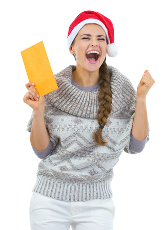 Happy young woman in sweater and christmas hat with letter rejoicing