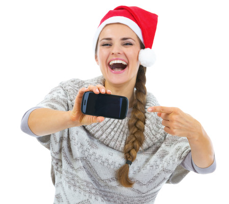 Closeup on young woman in sweater and christmas hat pointing on cell phone Stock Photo - 22514276