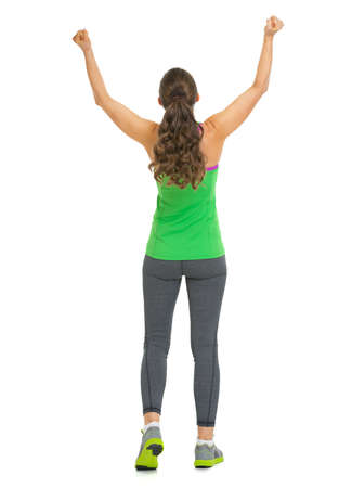 Full length portrait of happy fitness young woman rejoicing success . rear view photo