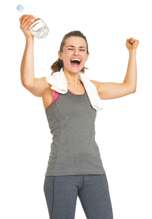 Happy fitness young woman with bottle of water rejoicing success