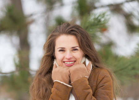 citypark: Portrait of happy young woman against fir-tree in winter outdoors