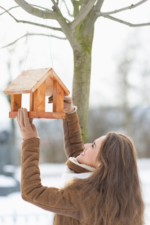lady bird: Happy young woman adding meal into bird feeder Stock Photo