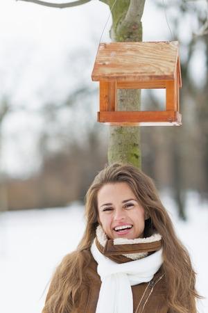 wintering: Portrait of smiling young woman standing under bird feeder in winter park
