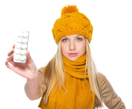 blister package: Serious girl in scarf and hat showing blister package of pills Stock Photo