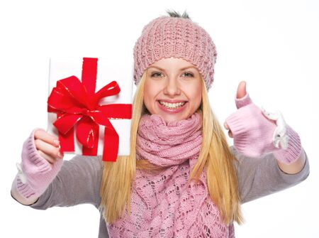 Smiling girl in winter clothes showing christmas presenting box and showing thumbs up photo