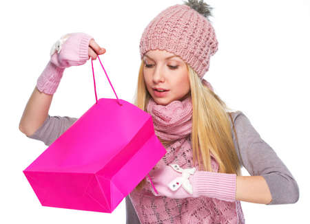 Curious girl in winter clothes looking into christmas shopping bag Stock Photo - 22519265