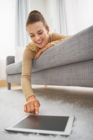 Happy young woman using tablet pc while laying on sofa