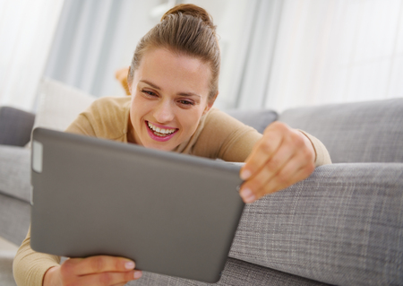 topicality: Smiling young woman using tablet pc while laying on sofa