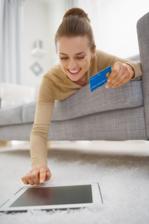 Happy young woman with credit card using tablet pc while laying on sofa photo