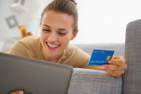 Smiling young woman with credit card using tablet pc while laying on sofa photo
