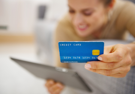 topicality: Closeup on credit card in hand of young woman laying on couch with tablet pc