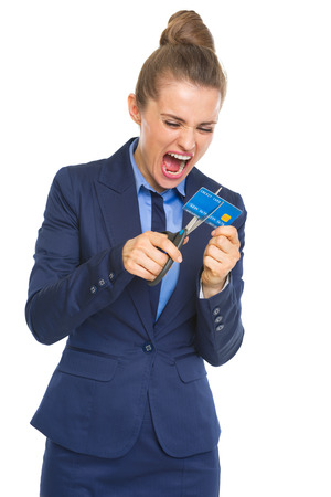 Angry business woman cutting credit card with scissors photo