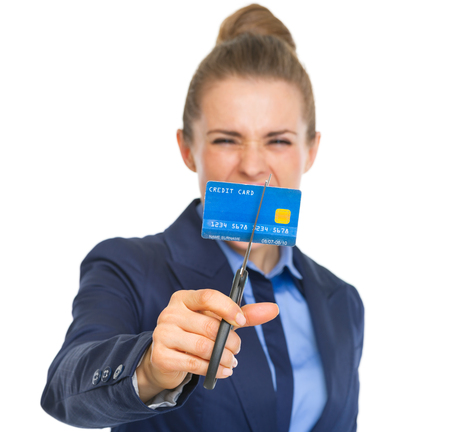Closeup on angry business woman cutting credit card with scissors photo