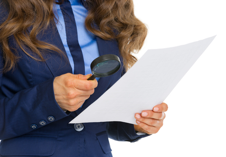 suspiciousness: Closeup on business woman examining document using magnifying glass