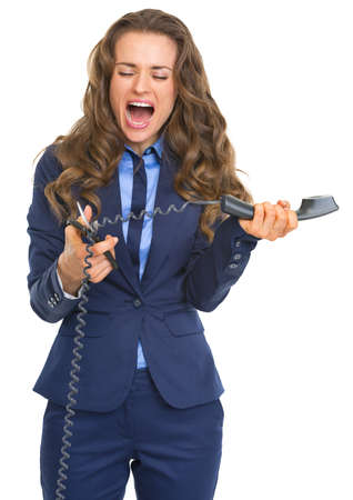Angry business woman cutting phone handset with scissors photo