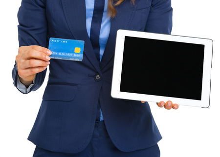 topicality: Closeup on business woman showing credit card and tablet pc blank screen