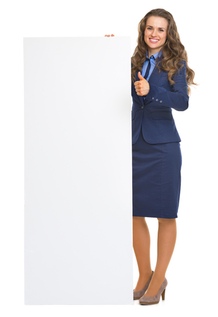 Full length portrait of smiling business woman showing blank billboard and thumbs up photo
