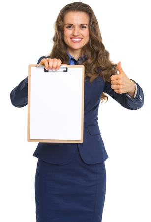 Happy business woman showing blank clipboard and thumbs up photo