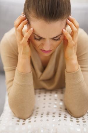 divan: Retrato de ama de casa joven tensionada que se sienta en el div�n