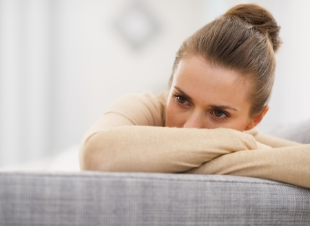 Stressed young woman sitting on sofa photo