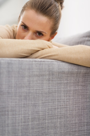 Stressed young woman sitting on couch photo