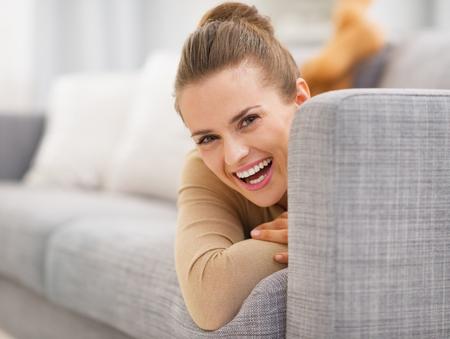 divan: Retrato de mujer joven y sonriente mirando desde divan Foto de archivo