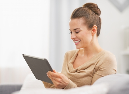 topicality: Happy young housewife sitting on sofa and using tablet pc