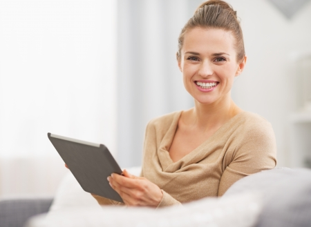 topicality: Smiling young woman sitting on sofa and using tablet pc