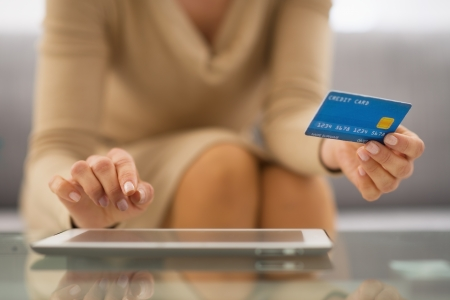 room card: Closeup on woman with credit card using tablet pc
