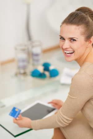 Smiling young housewife with credit card using tablet pc in living room Stock Photo - 22665662