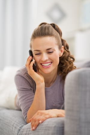 Smiling young woman laying on couch and talking mobile phone photo