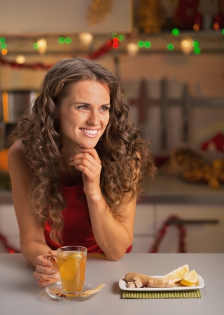 Happy young woman drinking ginger tea in christmas decorated kitchen Stock Photo - 22887969