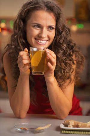 Happy young woman drinking ginger tea with lemon Stock Photo - 22887972