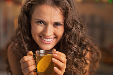 Smiling young woman drinking ginger tea with lemon Stock Photo - 22887973