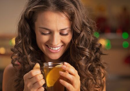 Happy young woman enjoying drinking ginger tea with lemon Stock Photo - 22887725