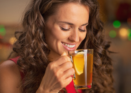 Happy young woman drinking ginger tea with lemon Stock Photo - 22887727